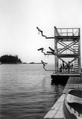 [People diving off a three level diving platform at] Eagle Harbour, on Howe Sound