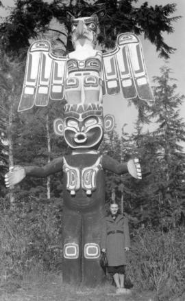 [Woman standing beside totem pole]