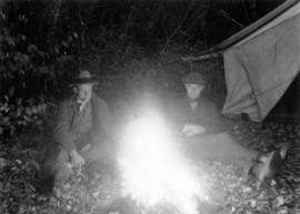 [James Crookall and another man sitting beside a campfire]