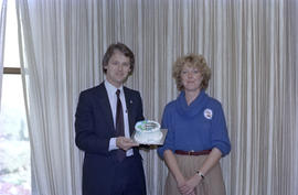 Alderperson Gordon Campbell and a member of Centennial staff holding a cake