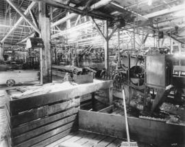Cannery with an fish processing machine in the foreground