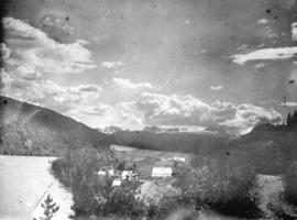 [View of group of buildings near shore, showing mountains in the distance]