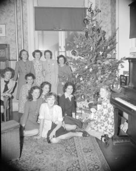 [Group portrait of B.C. Telephone employees sitting by a Christmas tree]