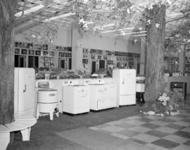 [Interior view of Kelly's appliance store, showing store decorated with plants and trees]