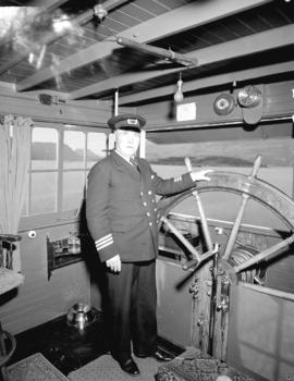 "Captain McDonald at wheel [of the ""Tutshi""]"