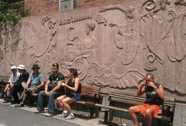 People sitting on benches against mural in Montreal Chinatown