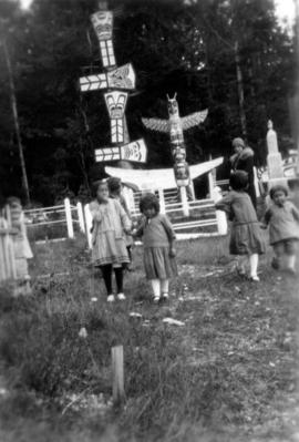 [First Nations children and a woman in front of totem poles at] Alert Bay