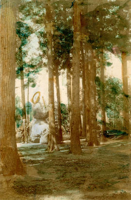 [View of man standing next to statue in the forest]