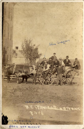 Alex Godfrey with a group of men on a farm wagon, Manitoba