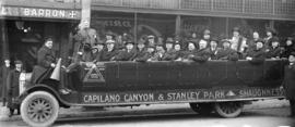 [Group of men and women in a Triangle Tour Car in front of the Hotel Barron]