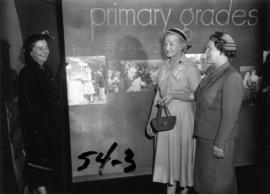 Ladies posing next to B.C. Department of Education exhibit in P.N.E. B.C. building