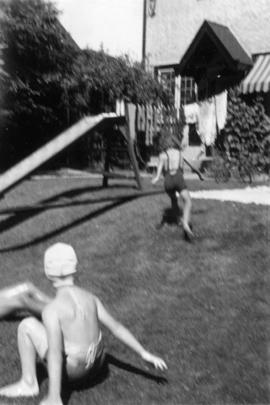 Children playing on lawn in bathing suits