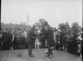 A trophy being handed out with a crowd watching