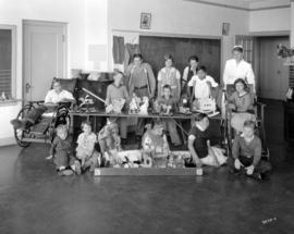 [Group portrait in recreation room of the Crippled Children's Hospital - 250 West 59 Avenue]
