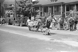 [Men with a one-wheeled cart in parade on Georgia Street]