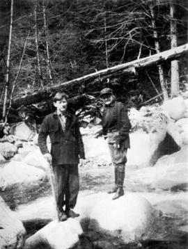 [Unidentified man and woman standing on large rocks in river near Summit Lake]