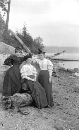 [Three women assembled around driftwood on Stanley Park beach near Brockton Point]