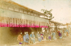 [View of a people sitting along a road in front of a building]
