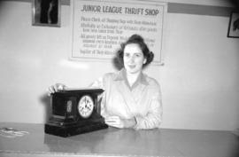 Store clerk, Miss Nora Jane Harrison, with clock at the Junior League thrift shop]