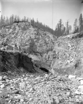 [Men digging diversion tunnel through rock bluff at east end of Coquitlam Dam site]