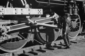 [Engineer oiling locomotive wheels]