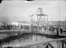A man diving off a high board with a crowd watching