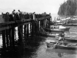[Men holding fishing nets between a dock and rowboats]