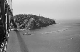 [View from the Lions Gate Bridge of a tug towing a logboom]