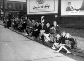 [People line a street to see King George VI and Queen Elizabeth]