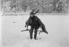 Man with rifle carrying a deer