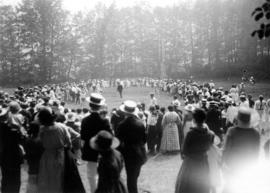 [Crowd lining a field to watch a sporting activity]