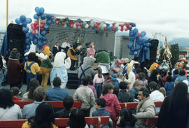 People and mascots crowd around Chevron Stage at PNE grounds