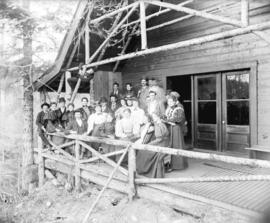 [Men and women assembled on porch of Capilano Canyon cottage built by George Grant McKay]