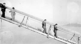 Karl Haspel and three other men walking down the cable line on the Lion's Gate bridge
