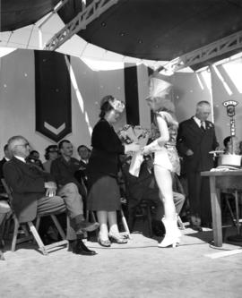 Majorette presenting flowers to the wife of Lieutenant Governor C.A. Banks on stage at 1947 P.N.E...