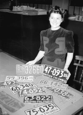 [Miss Alice North with a collection of old license plates at the Motor Vehicle Testing Station on...