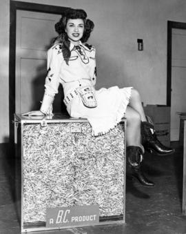 [Woman dressed as a cowgirl sitting on a crate of matches]