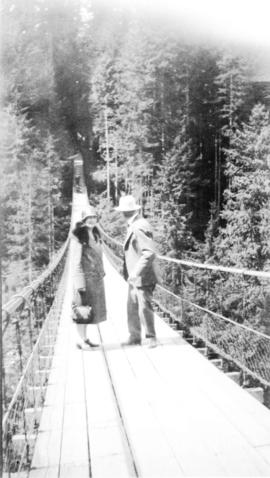 [L.D. Taylor and unidentified woman on the Capilano Suspension Bridge]