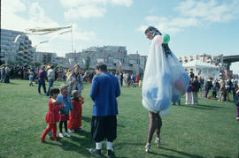 Woman on stilts interacting with children at Fool's Day Parade