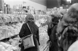 Interior of unidentified grocery store with shoppers, clerks, and stock