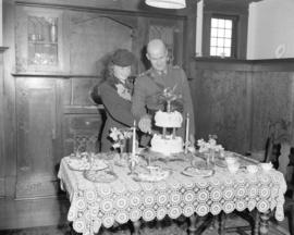 [William Bruhn and Margo (nee Skelton) cutting wedding cake]