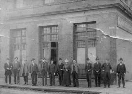 [A group of people standing in front of Oppenheimer Bros. Wholesale Grocers building at Powell St...