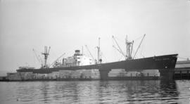 S.S. World Legion [at dock, with lumber-filled barges alongside]
