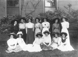 [Group of young women assembled on lawn outside house]