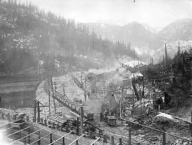 "Lake Buntzen tunnel enlargement [showing] train load of ""muck"" leaving west portal"