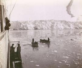 "[Rowboats from the S.S. ""Queen"" near a glacier]"