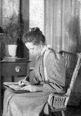 [Winifred Mabel Pierce sitting by a table writing in notebook]