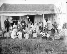 [Men and women assembled on porch of Linn's cottage]