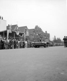 [Soldiers in a tank passing by crowds and a stage in a military parade along Burrard Street]