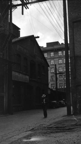[Man standing in lane near second electric power house in Vancouver near Pender and Abbott Streets]
